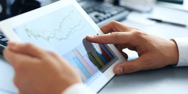 Hands operating a tablet with graph and charts