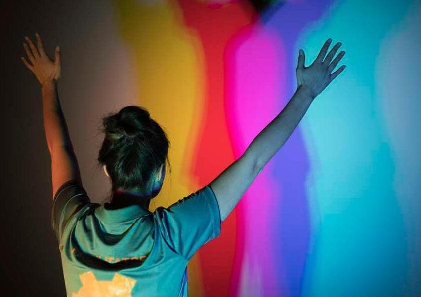 Woman raising hands in front of colorful backdrop