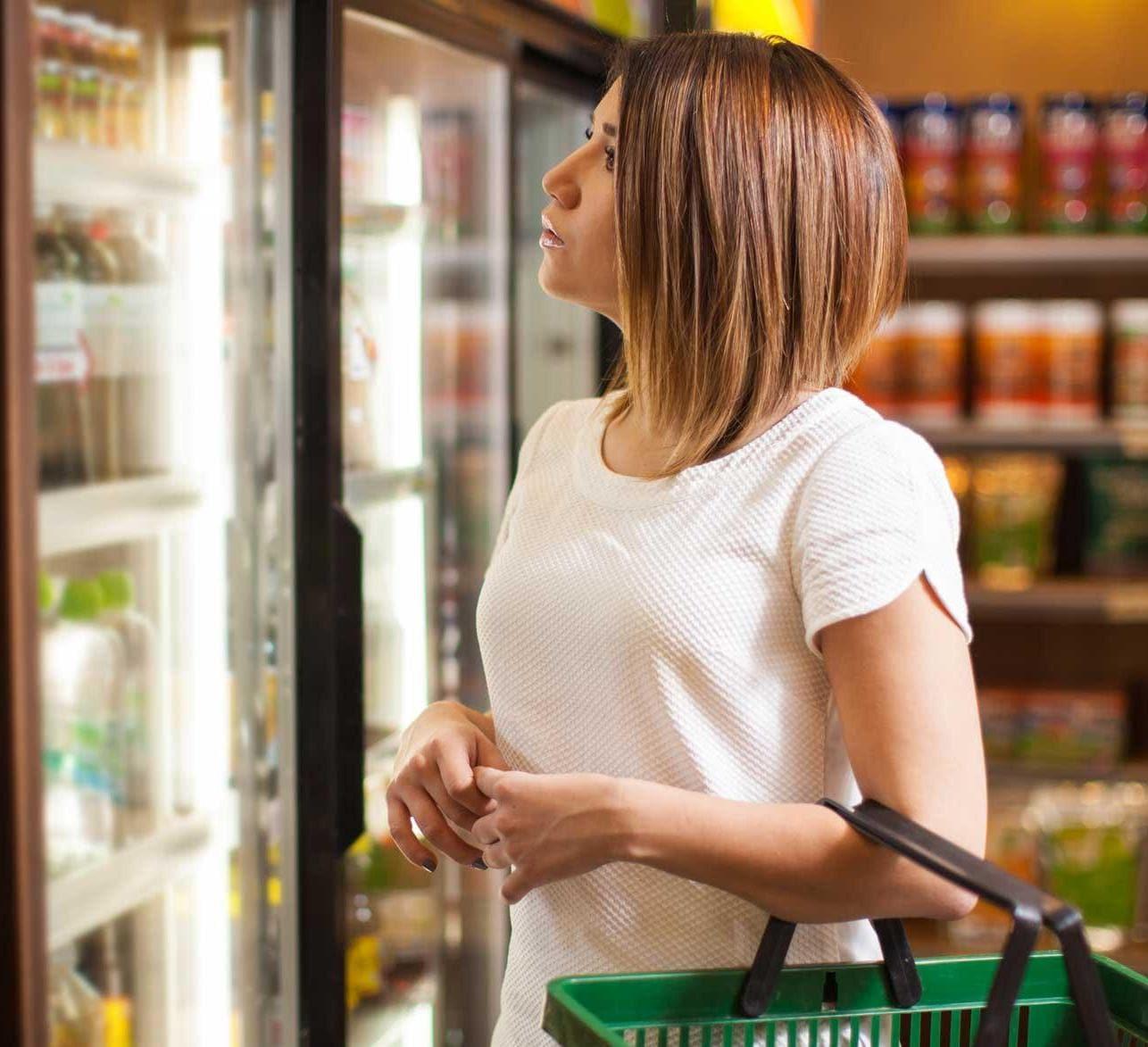 Woman shopping in supermarket fridge