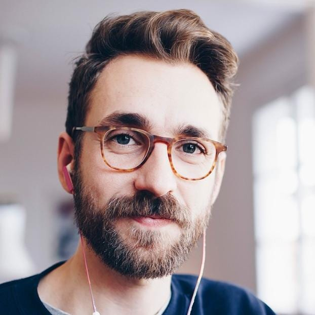 Man in glasses with beard and headphones
