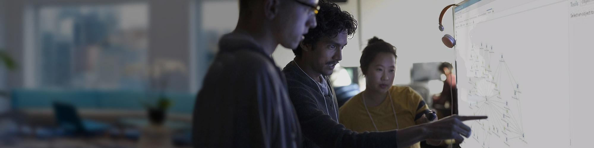 Group of young coworkers huddled around large computer monitor