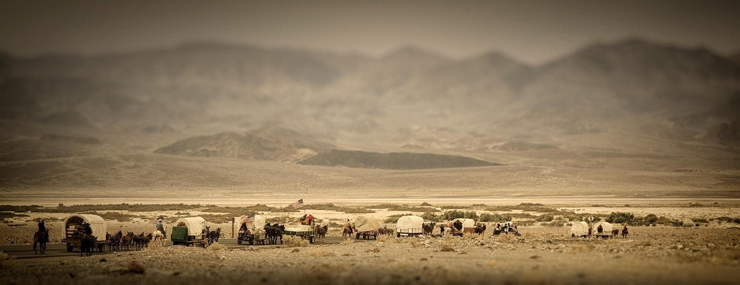 covered wagon train in desert