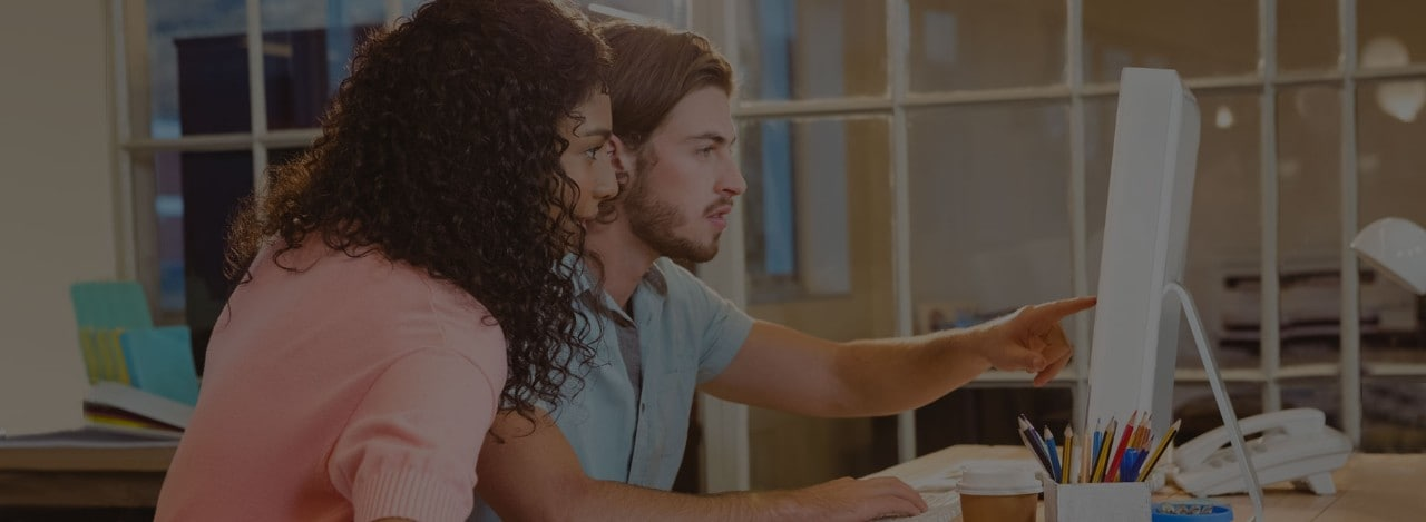 Young man and woman working together at laptop computer