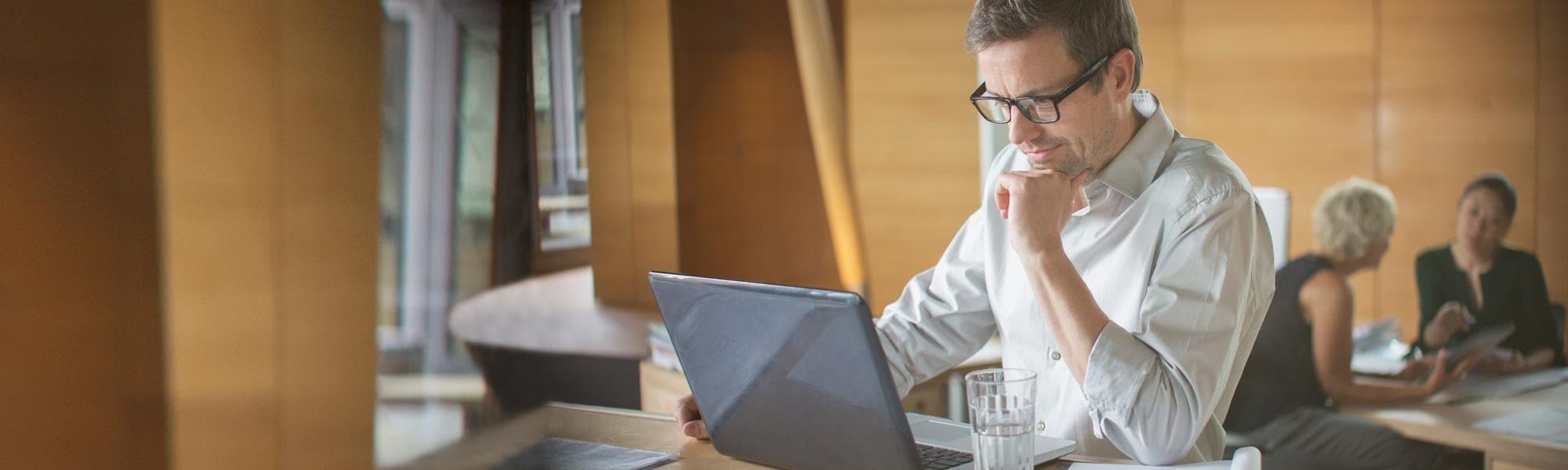 Se muestra a un hombre trabajando en una laptop en su escritorio