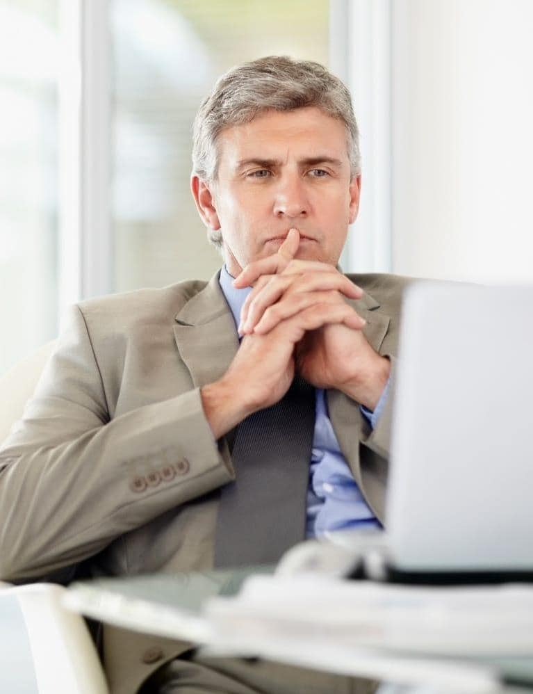 Middle aged business man at desk with laptop computer