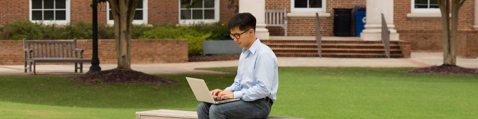 Student on Cary Academy campus sitting with laptop on lap