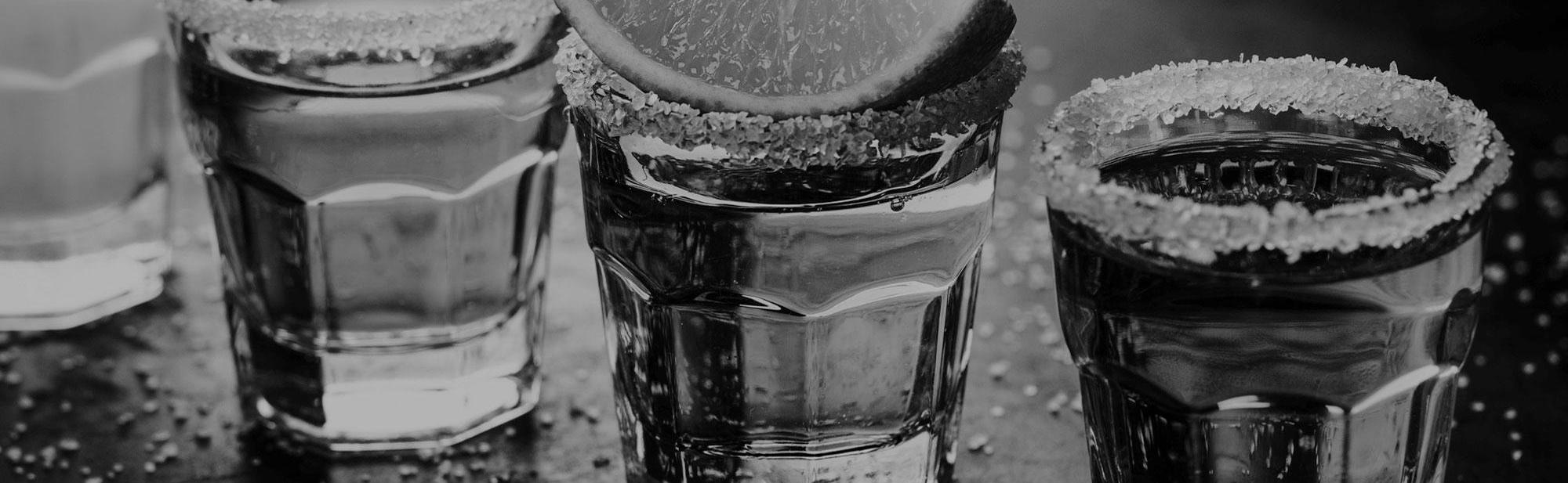 Tasty alcohol drink cocktail tequila with lime and salt on vibrant dark background. Closeup. Horizontal.