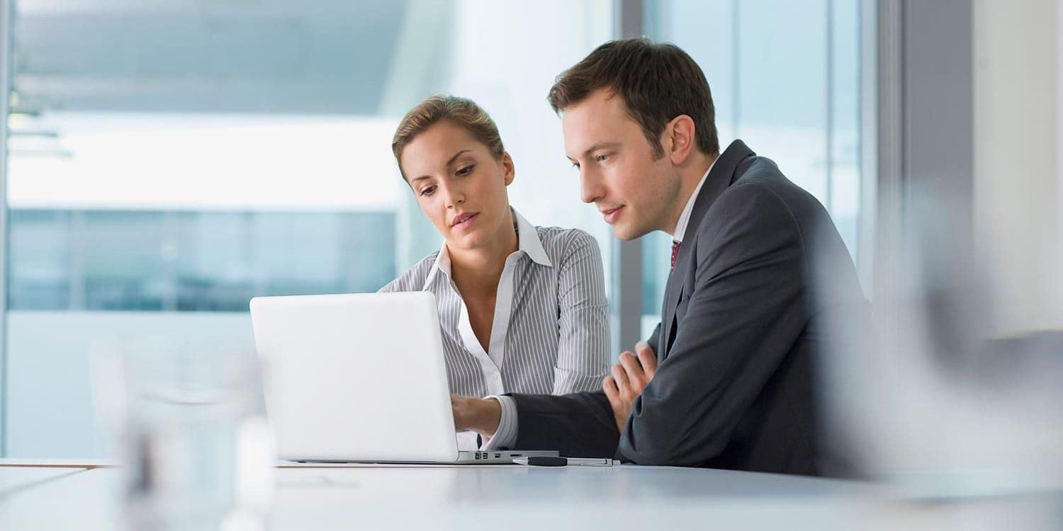 Man and woman working on laptop
