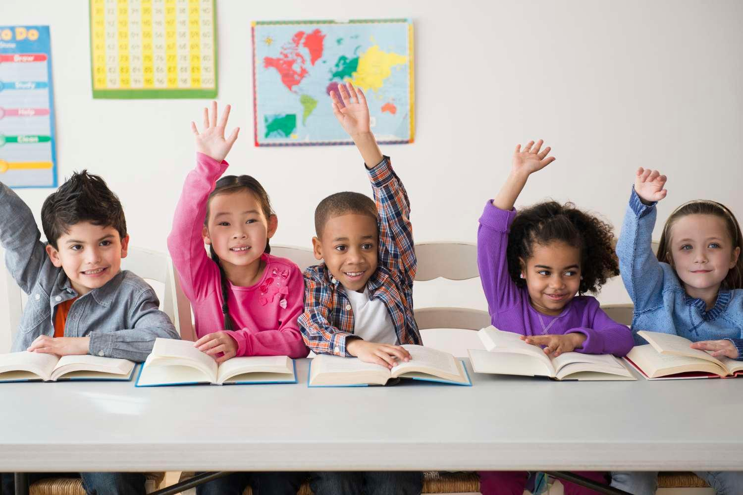 Young students in classroom with books and raising hands