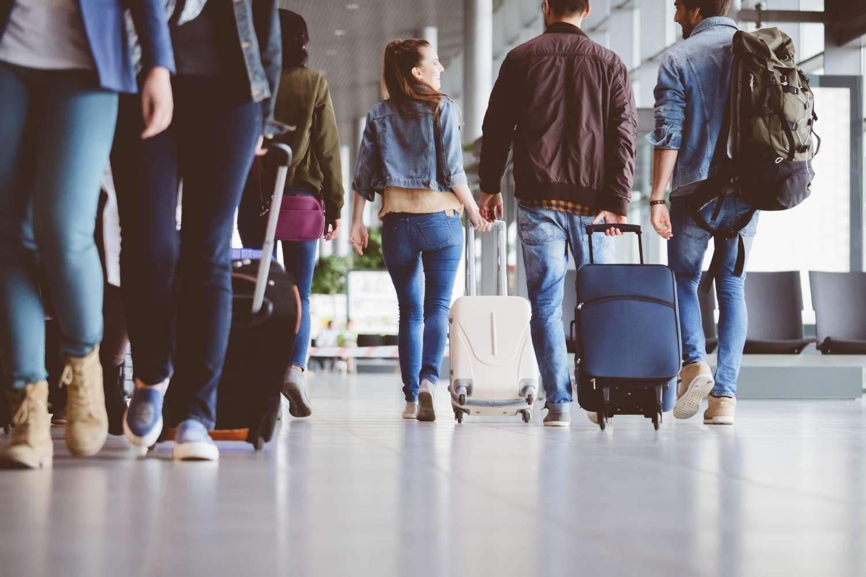 People in airport wheeling luggage