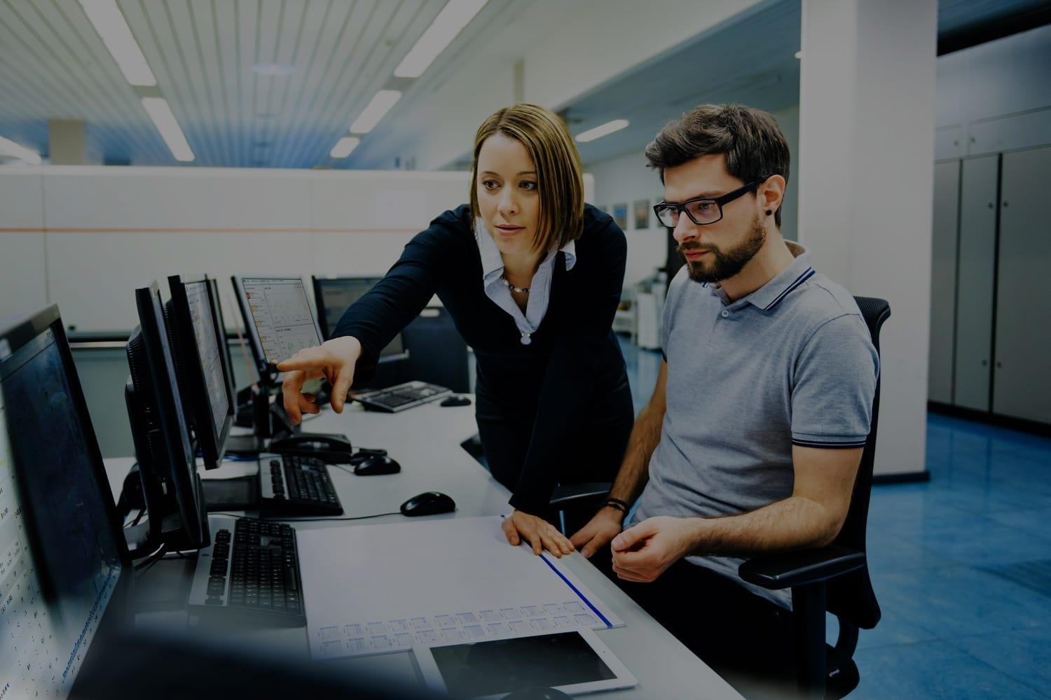 Two IT managers in command center study risk software