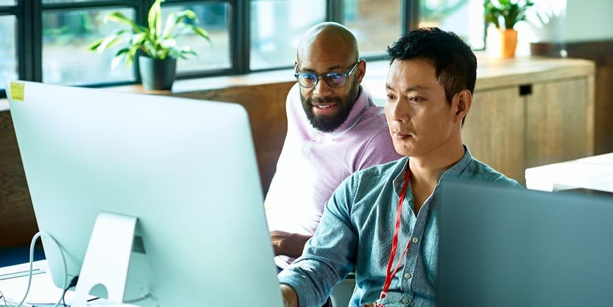 Two coworkers collaborate at desktop computer