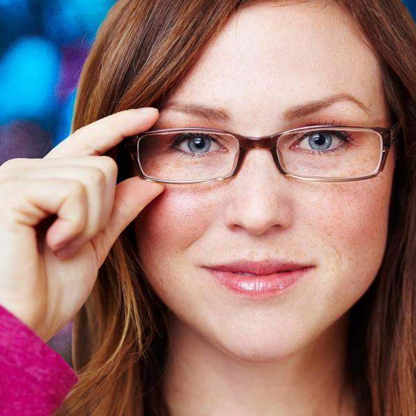 Close up of woman lifting her glasses
