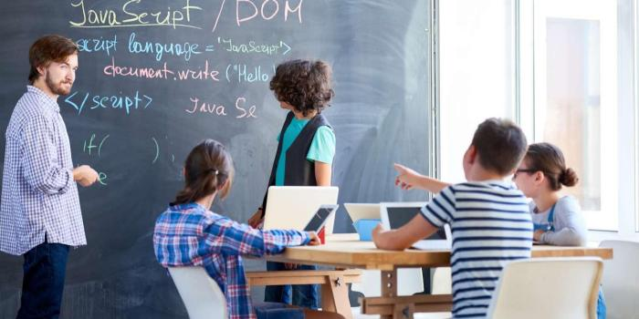 Instructor teaches young students programming language