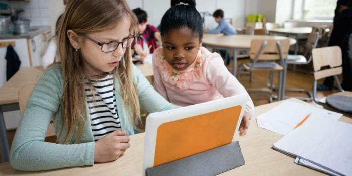 Two young female students use tablet device in classroom