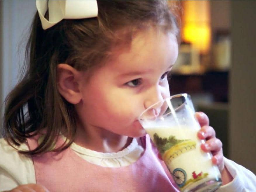 Young girl drinking fresh milk from glass