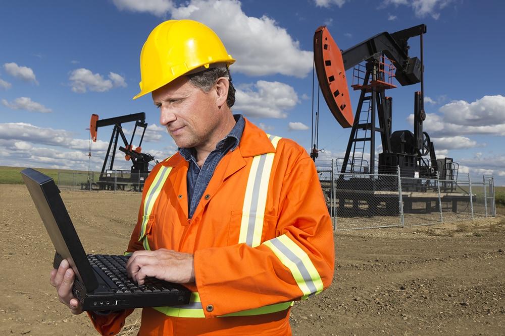 Man In Oil Field On Computer