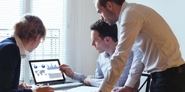 Two men and a woman looking at graphs and charts on a laptop