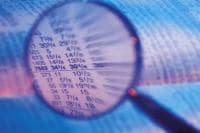 article Risk 20 20 ,78467915 Magnifying glass over newspaper stock market figures