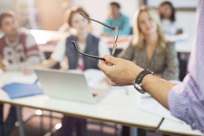 Professor teaching students with glasses in hand