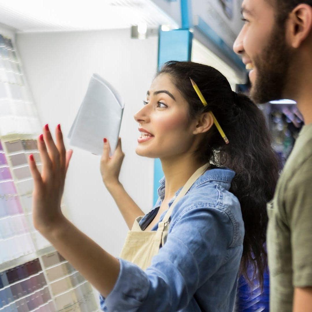 Couple regardant des nuanciers de peinture dans un magasin