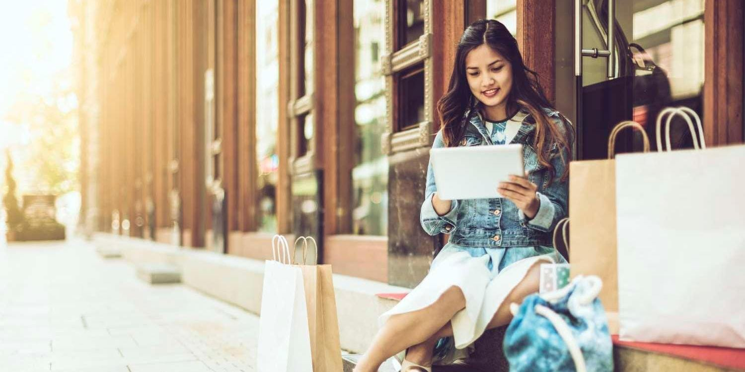 Woman with shopping bags sitting outside storefront looking at tablet device