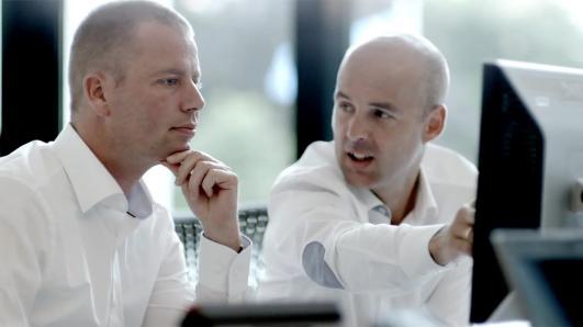 Two businessmen working at desktop computer
