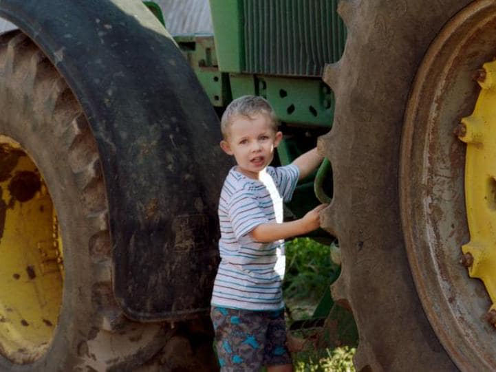 Young Lauderdale boy playing near tractor