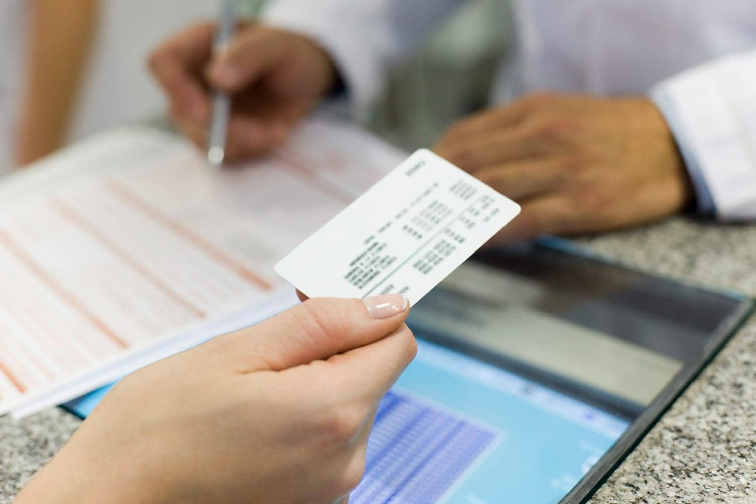 Patient using health insurance card