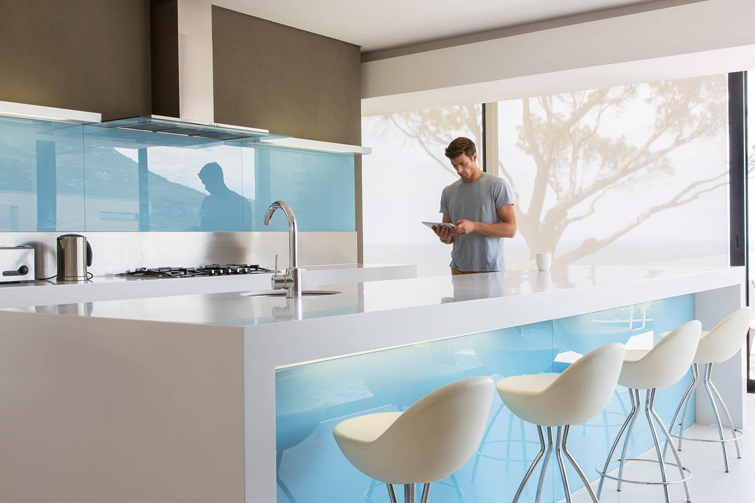 Man standing in kitchen looking at tablet