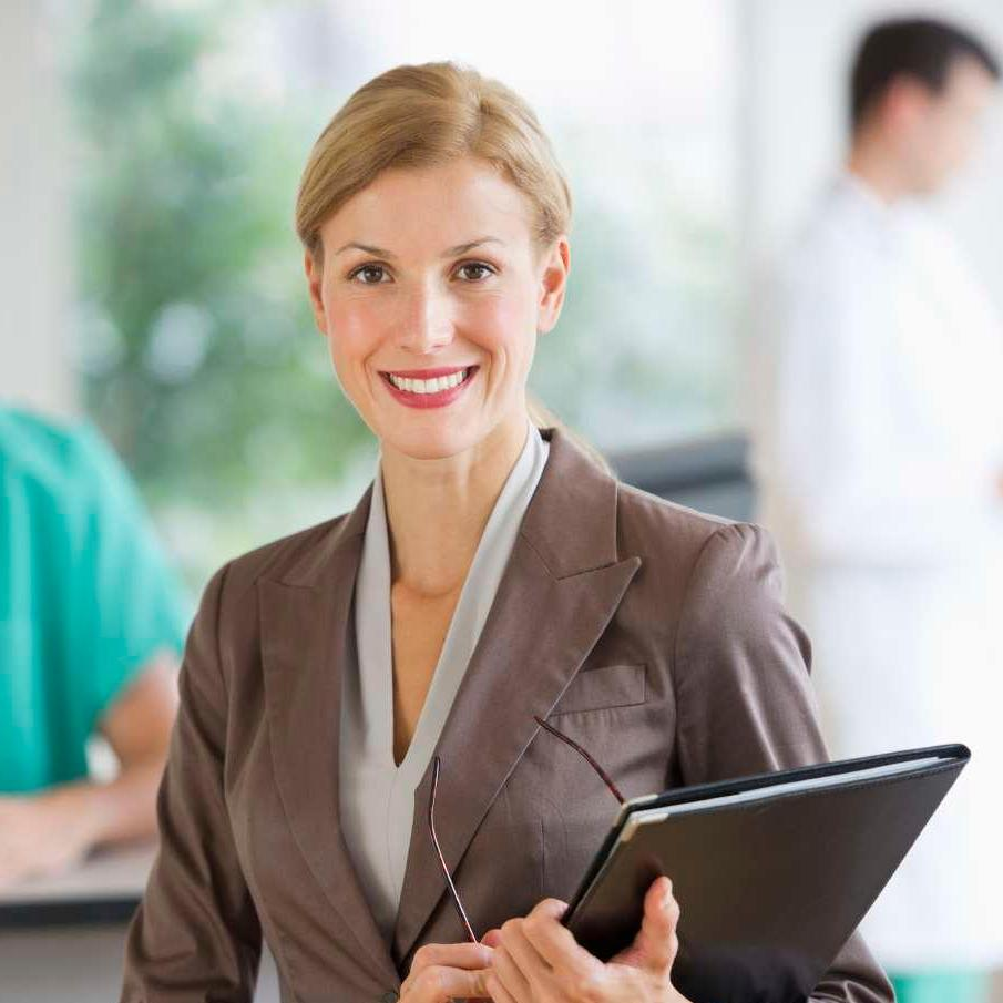 Woman with folder in hospital with doctors in background