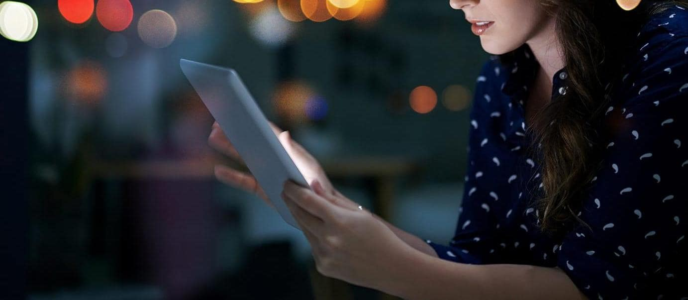 Young businesswoman working late on a digital tablet in an office