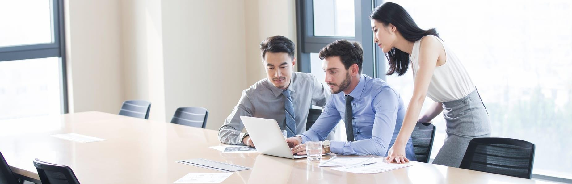 Young business colleagues study data on laptop