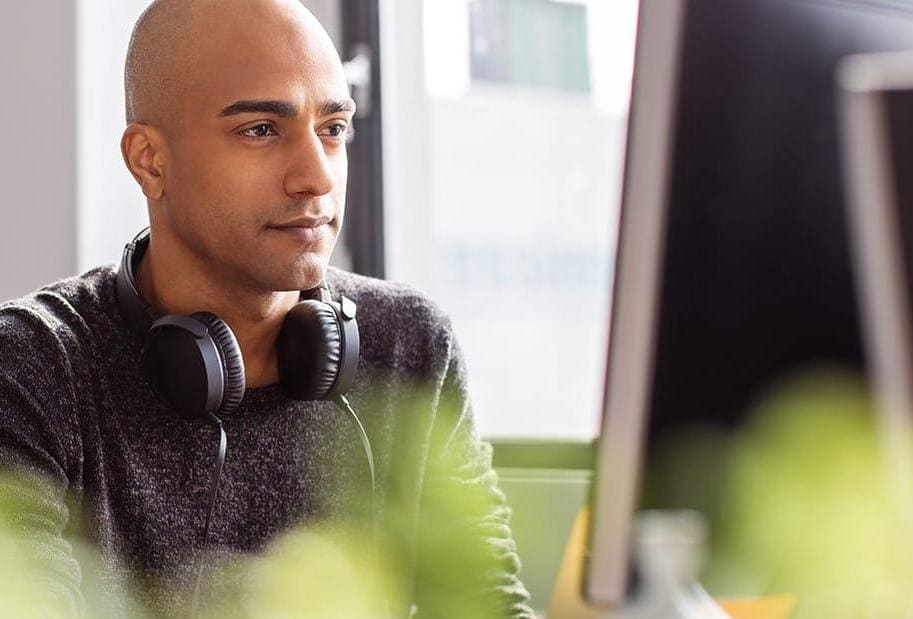 Business man with headphones working on desktop pc in office