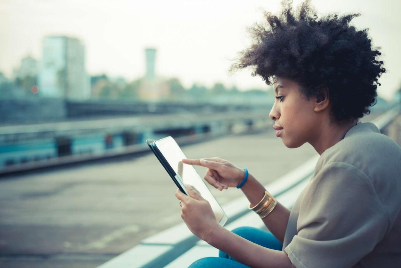 Young woman using touchscreen on digital tablet on city rooftop