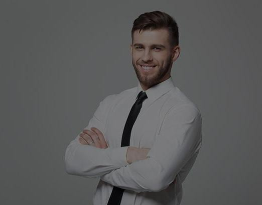 Young business man smiling at camera and crossing arms