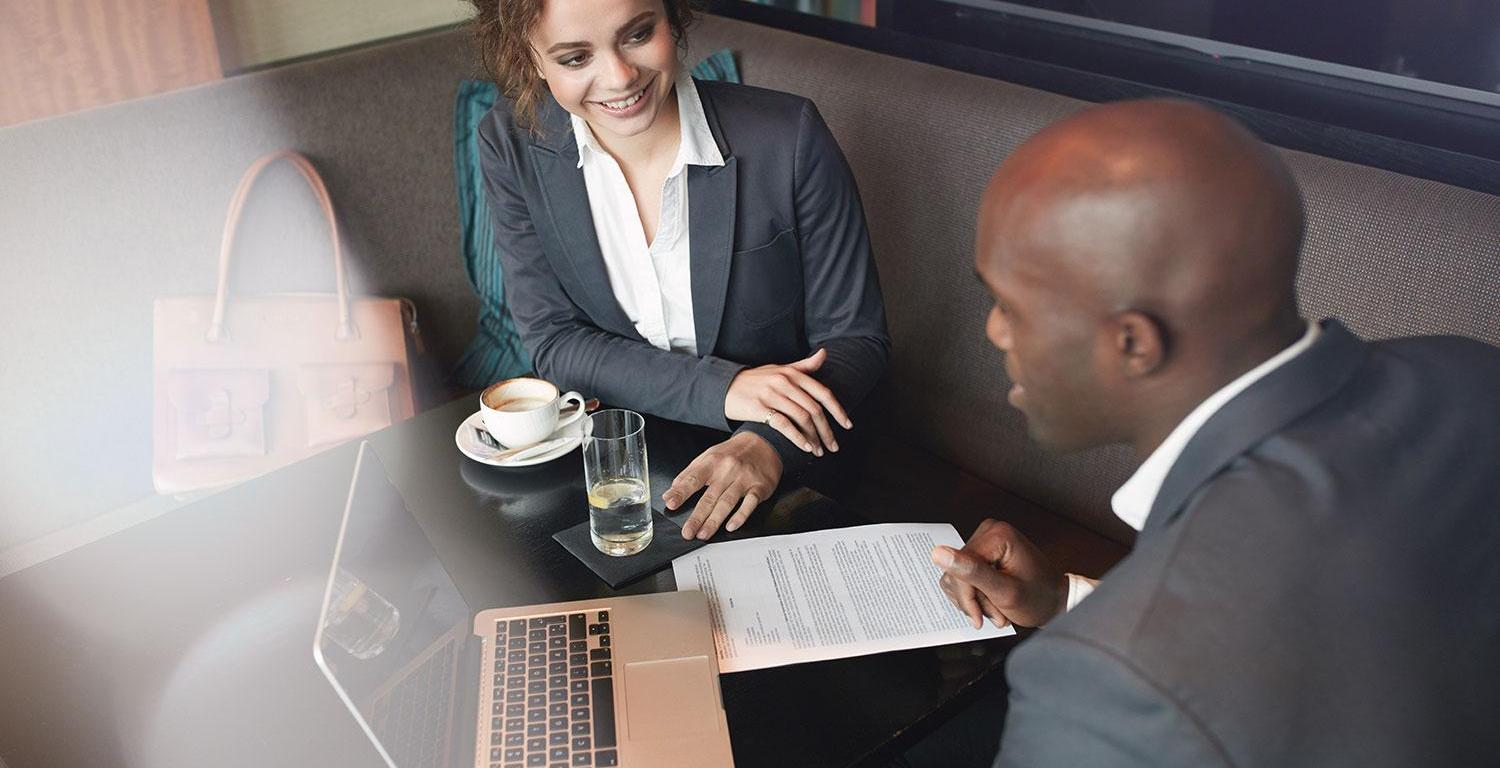 Businessman and woman talking over coffee with paperwork and laptop