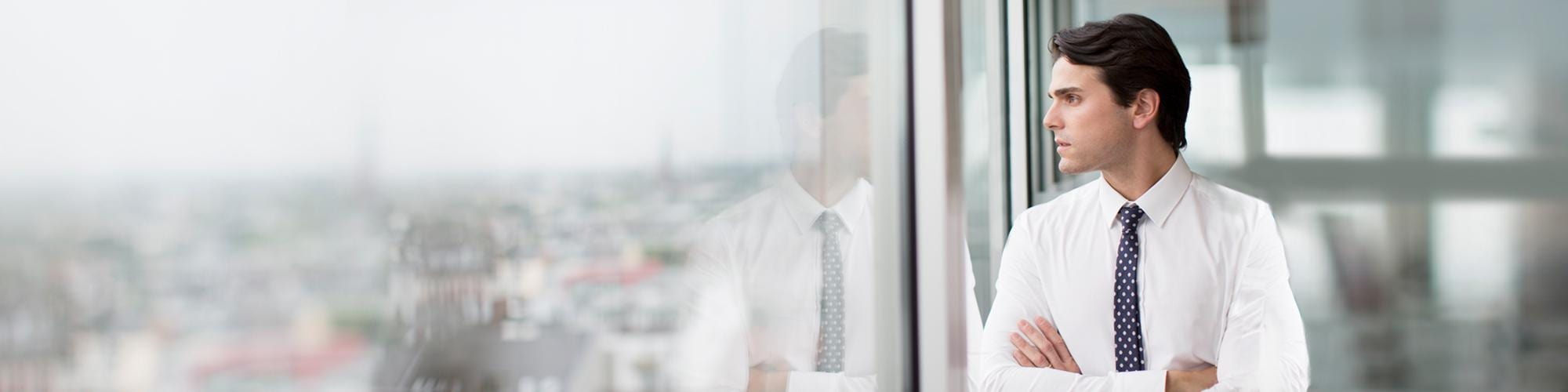 Man wearing white shirt and tie looking out a window