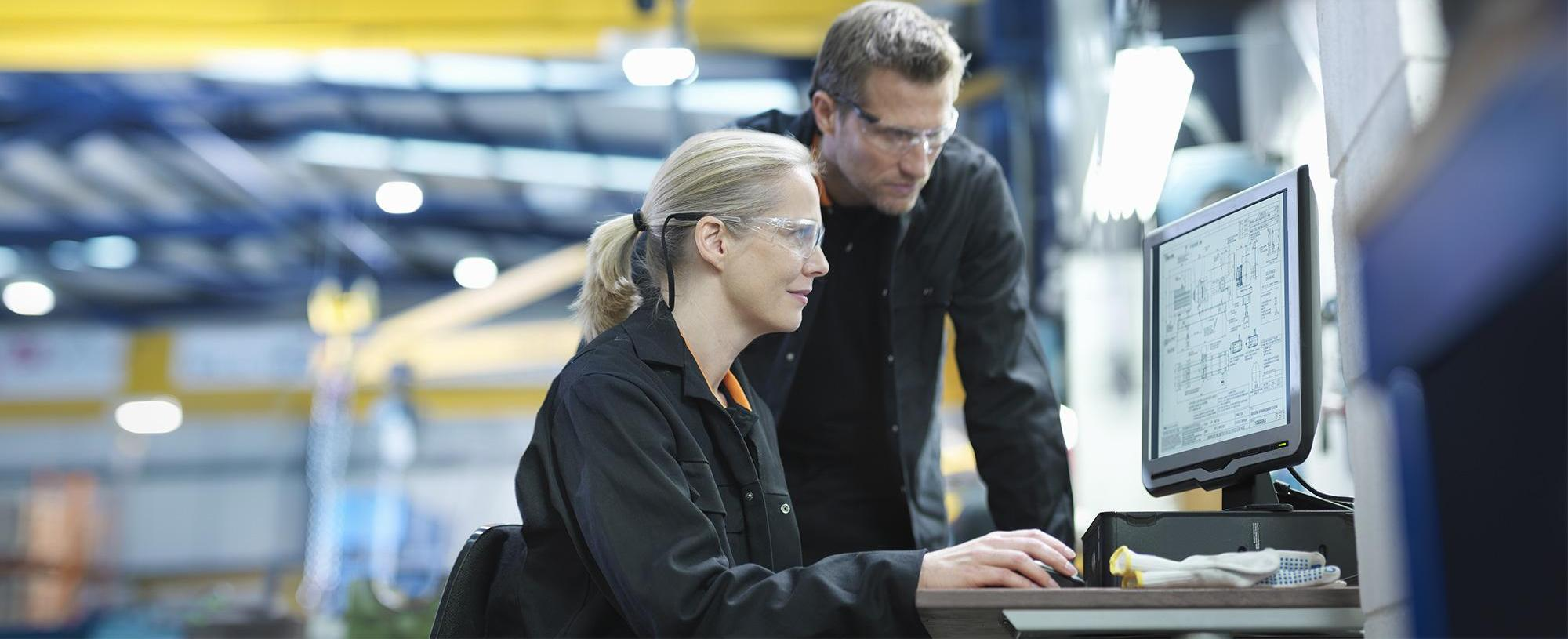 Man and woman in front of computer screen in factory
