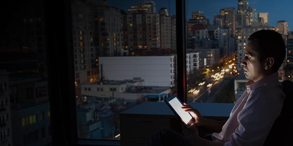 man looking at device with dark city background