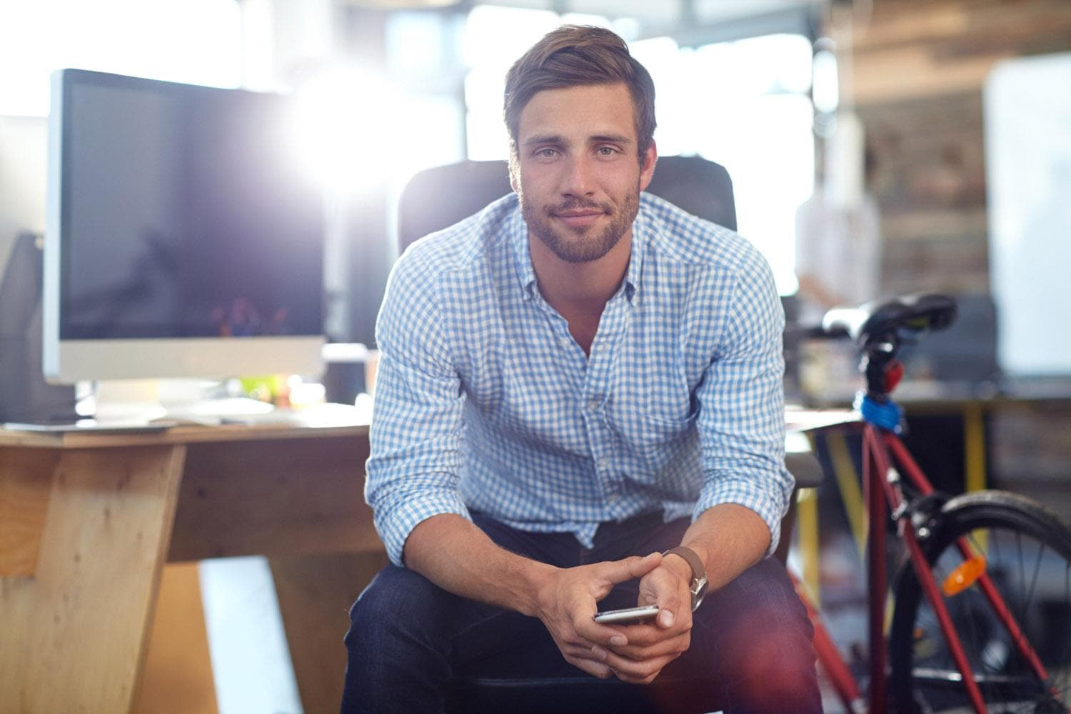 Young man in office looking directly at camera