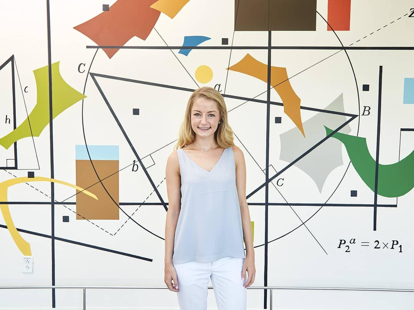 SAS intern Kate standing in front of a colorful background