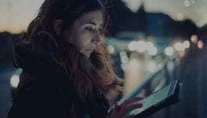Mid adult woman using digital tablet touchscreen on street at dusk