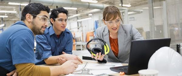 Two men in blue shirts and an executive woman in manufacturing setting looking at computer