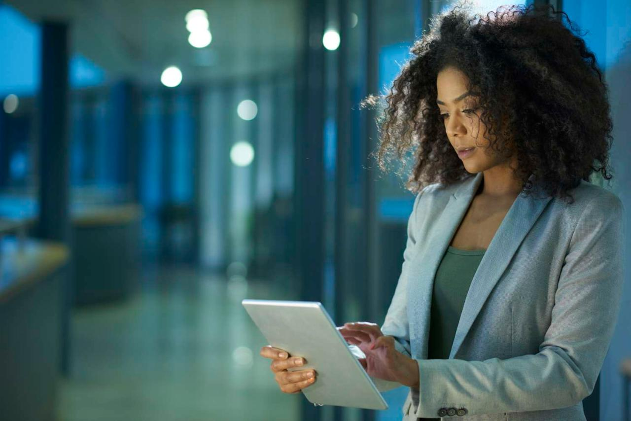 Business woman in gray suit using tablet in office at night