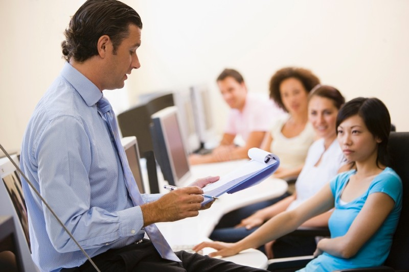 Instructor lecturing to class in computer lab