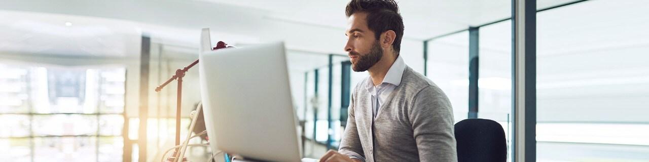 Pria di kantor sedang bekerja menggunakan komputer
