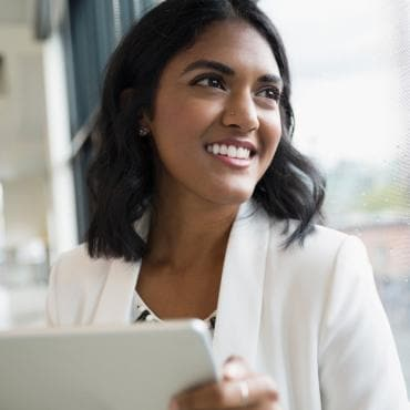 Young business woman with tablet device looking out window