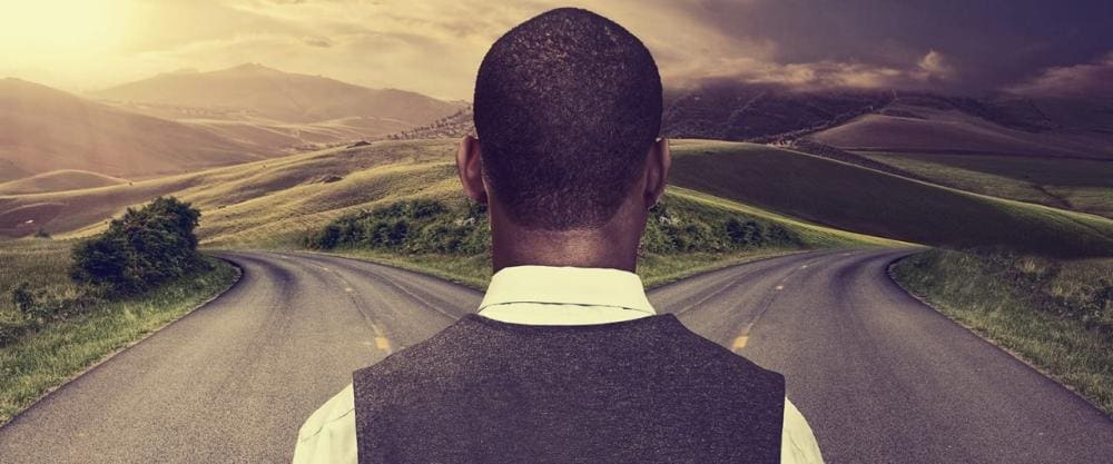 Young businessman standing at crossroads