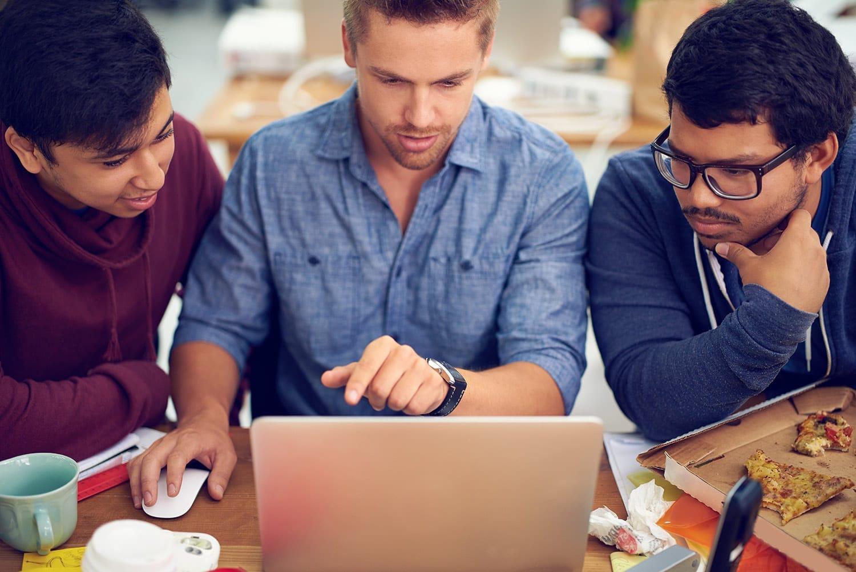 Three young men analyzing data on laptop